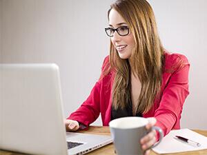 Kobieta przy laptopie z kawą
