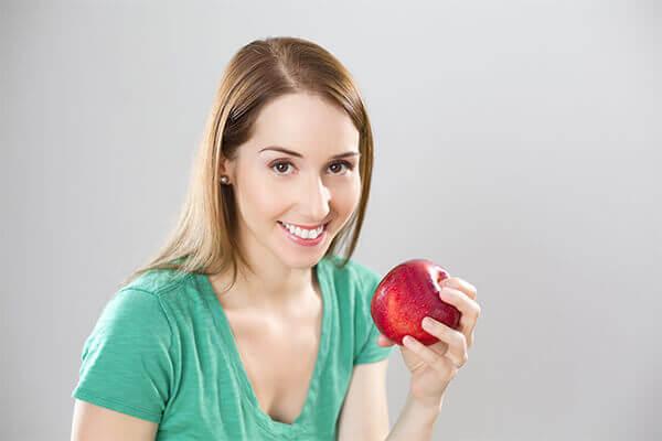 kobieta na zdjęciu trzyma jabłko i uśmiecha się pokazując przebarwienia zębów
