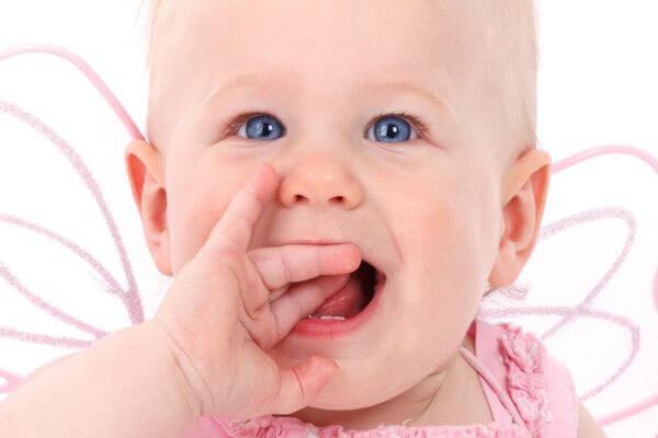 Objawy ząbkowania - dziecko wkłada rączki do buzi